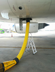Yellow air pipe lay on airport ground for airplane conditioning