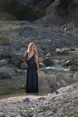 Nice young woman in black dress posing when standing in the river