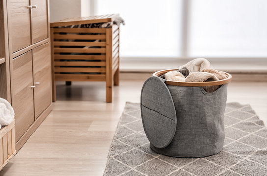 Laundry basket with dirty towels on floor in room