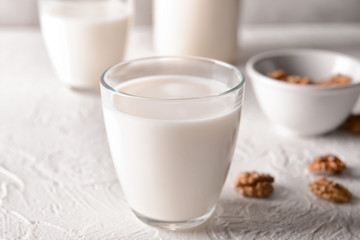 Glass of tasty milk on white table