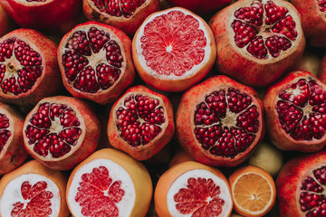 Red ripe pomegranates and grapefruit , copy space, top view.many pomegranate cut in half, pomegranate background.Background, citrus fruits, vitamins.Flatlay view of orange, pomegranate.Toned