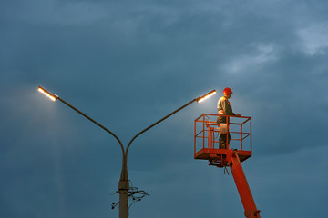Municipal worker with helmet and safety protective equipment installs new diode lights. Worker in lift bucket repair light pole. Modernization of street lamps. Technician on aerial device. Night duty