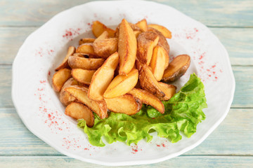 Plate of fried potatos with lettuce and paprika