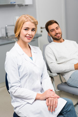 happy female dentist and handsome young client looking at camera in dentist office