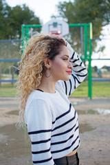 adolescente en el parque con canasta de baloncesto