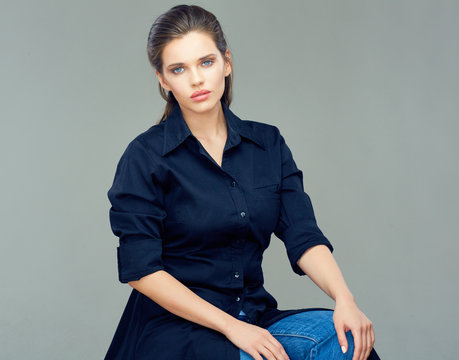Beautiful young woman dressed in black shirt dress.