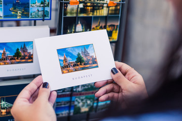 Tourist holds a postcard with a picture of a popular place in Budapest. This is a good souvenir after the trip. Fisherman's Bastion is a very visited historical place in Budapest