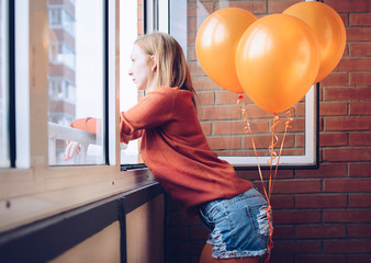 Girl in denim shorts and yellow pantyhose stands on the balcony with balloons