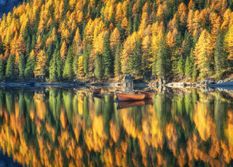 Wooden boats in Braies lake at sunrise in autumn in Dolomites, Italy. Landscape with fall forest, mountains, lake, water with reflection, trees with colorful foliage. Dolomiti. Travel in italian alps