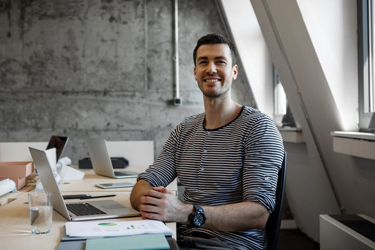 Portrait of young Caucasian smiling businessman sitting at office and looking at camera.