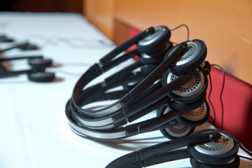 A set of headphones for simultaneous translation during negotiations in foreign languages . wireless multy language headphones set on the chairs in conference room
