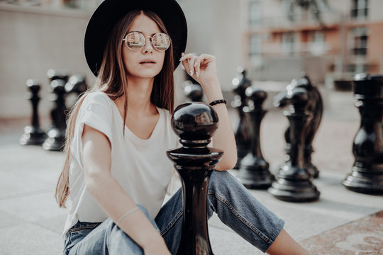Young trendy woman in hat and sunglasses standing on urban chessboars in the summer street