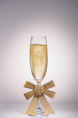 close up view of glass of champagne with ribbon on grey backdrop
