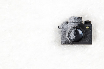 Frozen photo camera on the white snow background. Winter photography / photoshot