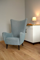Gray chair in the living room. Interior fragment