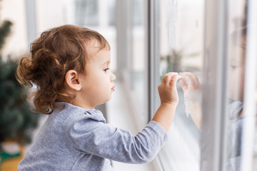 Cute little three years girl looking through window with holiday decoration.