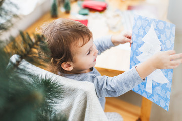 Cute little girl preparing christmas picture with christmas tree.