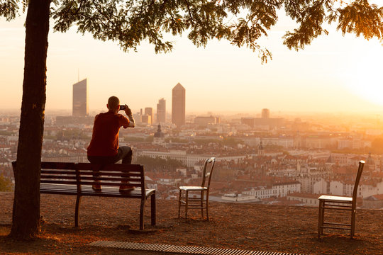 Man on a bench photograping the summer sunrise over a city. Lyon, France.