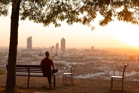 Man on a bench relaxing and enjoying the summer sunrise over a city. Lyon, France.
