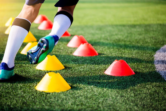 Soccer player Jogging and jump between cone markers on green artificial turf for soccer training.