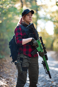 Portrait of an armed girl in the forest/Red-haired young woman with a backpack and a rifle in her hands against the background of the autumn forest