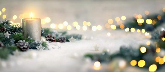 Dekoration für Weihnachten mit Kerze und Lichtern auf Schnee