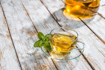 Teacup with mint on an old wooden table