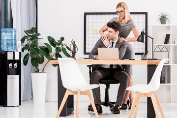 shot of businesswoman flirting with businessman at workplace in office