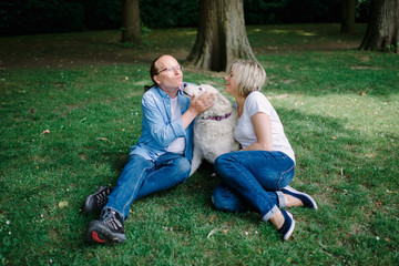 Adult couple sitting on the grass with a white hash