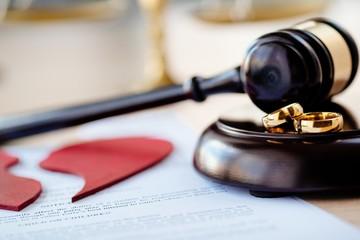 Two broken wedding rings on judge gavel