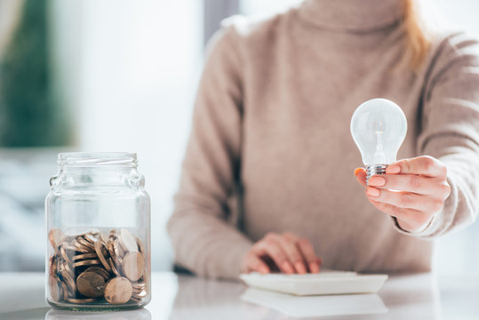 close-up view of glass jar with coins and woman holding light bulb