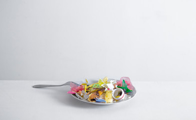 A plate with garbage instead of food. The concept of unhealthy food.