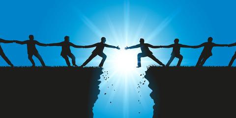 Deux groupes d'hommes se tiennent par la main pour se rejoindre et établir une connexion au dessus d'une brèche
