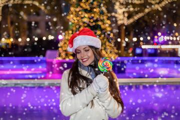 Attraktive Frau mit Weihnachtsmütze und buntem Lolli auf dem Weihnachtsmarkt bei Schneefall am Abend