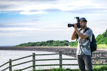 Closeup of Young handsome Professional photographer in white shirt with black backpack, taking landscape photos on the beach close to a wooden fence in a green nature with blue cloudy sky