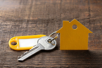 The concept of buying a home. Keys with a keychain and a house on a brown wooden background.
