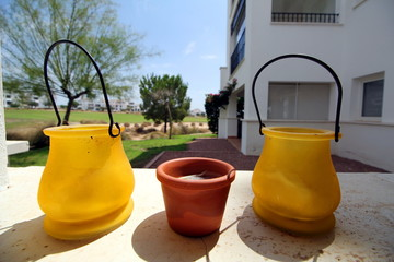 Small yellow and terracotta pots, on a stone ledge, with bright background of a golf course and apartments