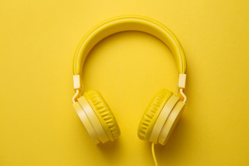 Yellow headphones on yellow background. Music concept. Wall mural