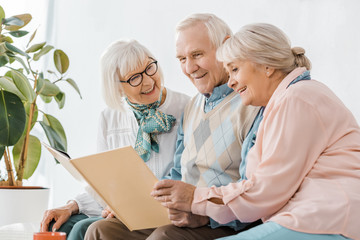 senior smiling people reading book together in nursing home