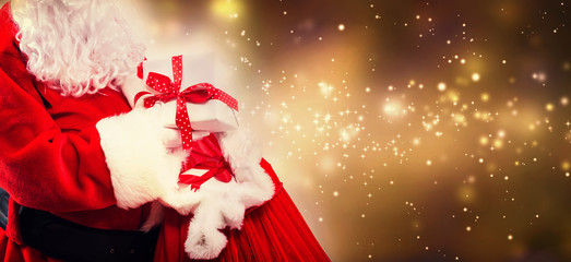Santa holding a present box from a red sack on a shiny light background