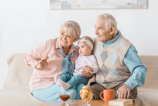 adorable grandparents sitting on sofa with toddler granddaughter