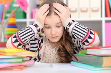 Portrait of a cute little girl doing homework