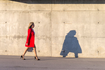 Blonde woman wearing red jacket walking on the street