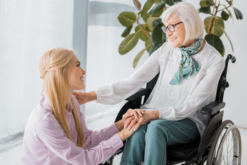 young woman sitting near senior woman in wheelchair