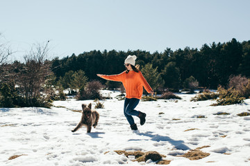 .Young and active woman playing with her nice dogs in the snow on a sunny winter day. Having fun. Pet friendly. Lifestyle.