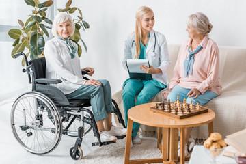 young smiling female nurse sitting on sofa and writing prescription to senior women
