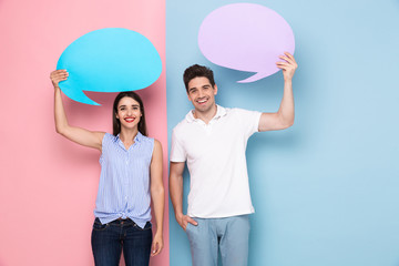 Image of european man and woman holding copyspace bubbles for announcement, isolated over colorful background