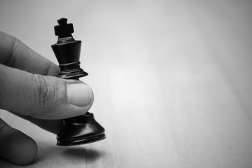 Close up of chess player makes a move the black king step forward. Business concept