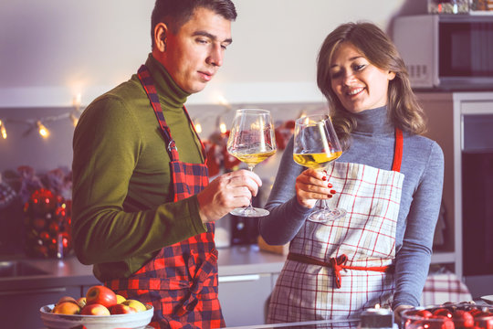 Couple celebrating Christmas in the kitchen and drink wine