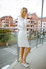 A young girl dressed in a bathrobe on the balcony. Outdoor background park.
